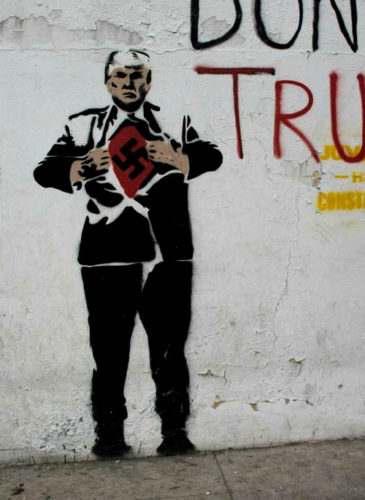 "A mural of U.S. President Donald Trump depicting him wearing a Nazi swastika covers a wall along a sidewalk in Caracas, Venezuela, Nov. 14, 2017, along with the Spanish message: ""We are those of peace."" (AP/Ariana Cubillos)"