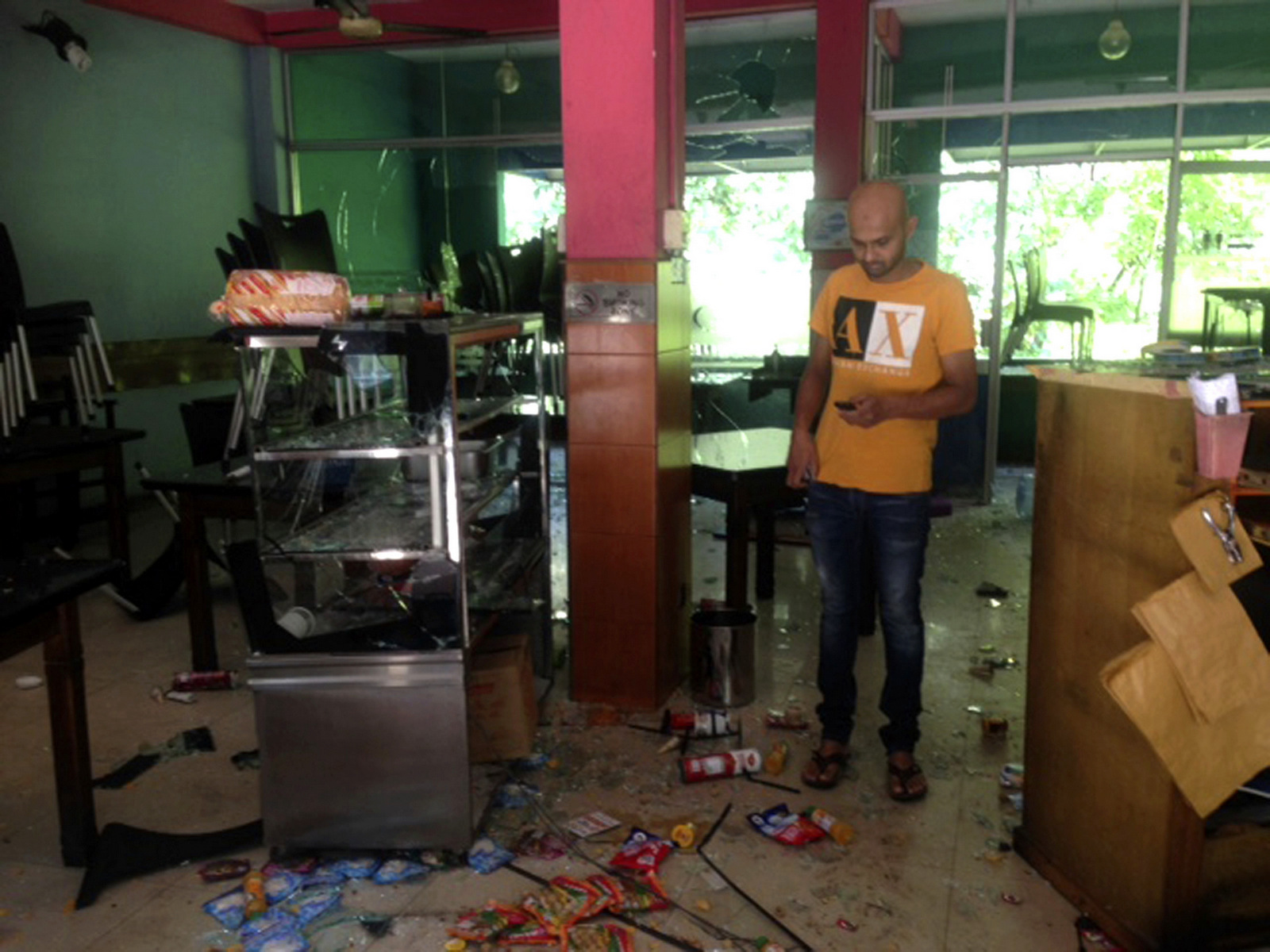 Mohamed Ramzeen makes a call from his mobile phone standing in his vandalized small restaurant in Pilimathalawa, Sri Lanka, March 8, 2018. About 50 people broke into Ramzeen's small restaurant destroying nearly everything they found, he said. Buddhist mobs swept through Muslim neighborhoods in Sri Lanka's central hills, destroying stores and restaurants despite a curfew, a state of emergency and a heavy deployment of security forces. (AP/Bharatha Mallawarachchi)