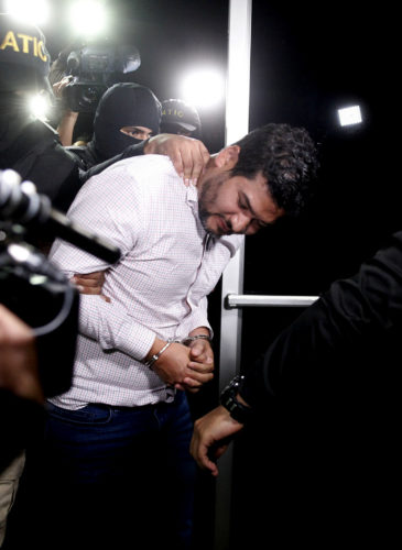 Roberto David Castillo is taken into custody by the police as he is walked to the Technical Investigation Agency in Tegucigalpa, Honduras, March 2, 2018. (AP/Fernando Antonio)
