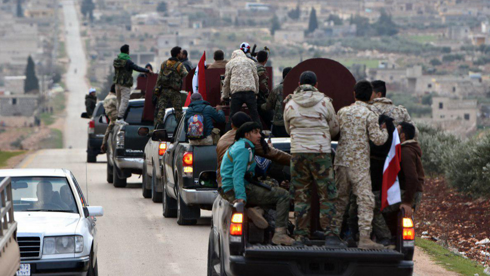 A convoy of militiamen loyal to the Syrian government on their way to aid the Kurds against Turkish forces, in the northern city of Afrin, Syria. (SANA via AP)