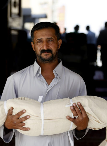 Qasim Ahmed Tahan carries the dead body of his 5-year-old son, Walid, who was killed in a bombing before burial in Najaf, Iraq, Sept. 14, 2013. (AP/Jaber al-Helo)