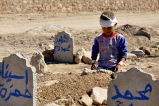 Ali Hamza, 8, sits at the graves of his brother, Mohammed, and sister Asinat, who were killed at their school when a suicide car bomb attack near Qabak elementary school in the Shiite Turkomen village of Qabak, Iraq, Oct. 7, 2013. (AP Photo)