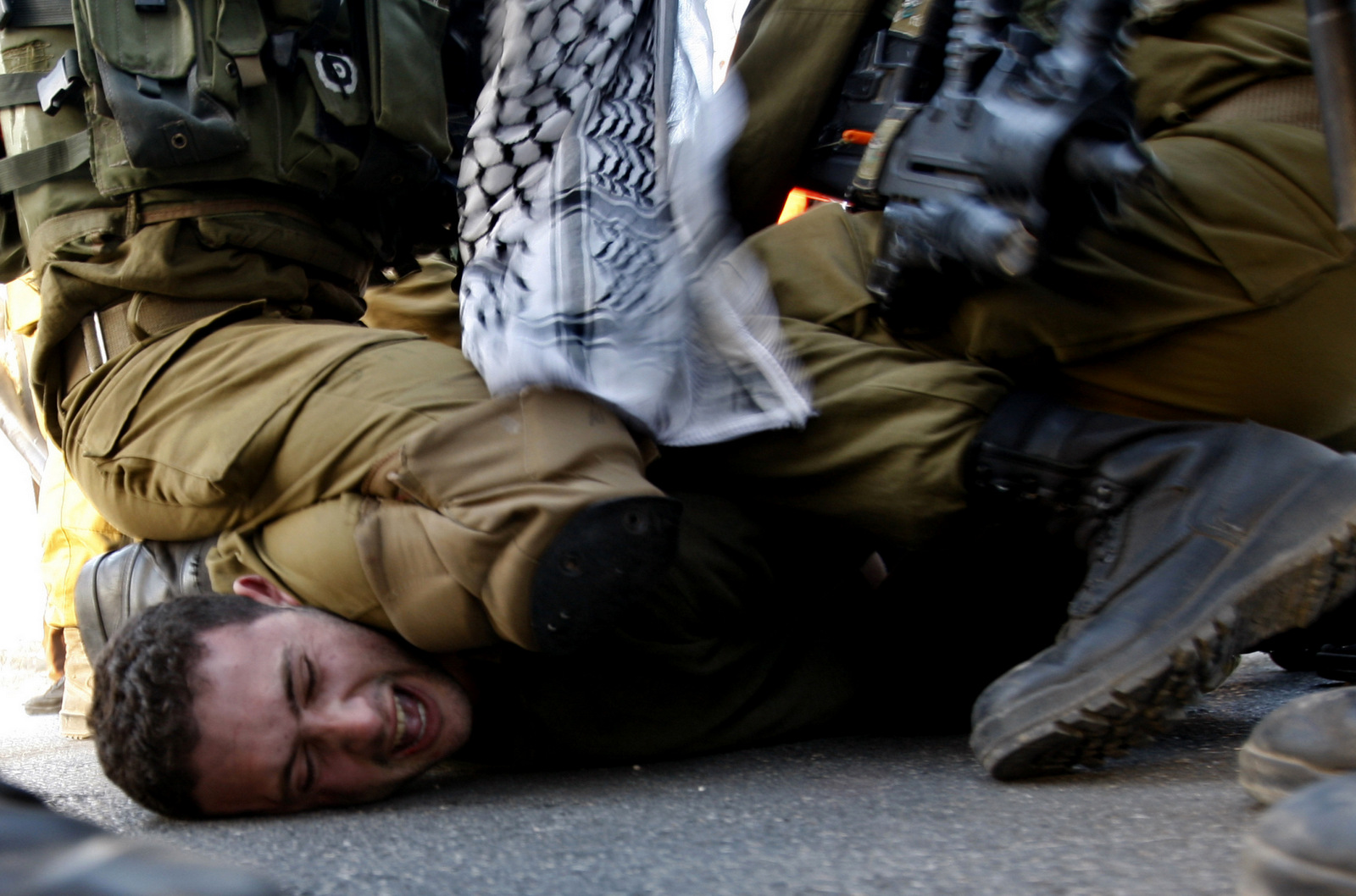 A Palestinians activist is detained by Israeli soldiers during a protest against the Prawer Plan to resettle Israel's Palestinian Bedouin minority near the Israeli settlement of Bet El, north of Ramallah, Nov. 30, 2013. (AP/Majdi Mohammed)