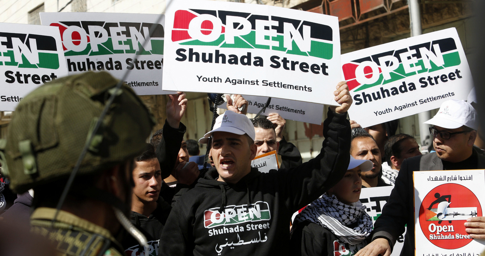 Protesters hold posters demanding the reopening of Shuhada Street in Hebron, Friday, Feb. 27, 2015. Israel closed Shuhada Street for Palestinians in 1994 after an Israeli killed 29 Palestinians and wounded over a 100 praying in a mosque. (AP/Nasser Shiyoukhi)