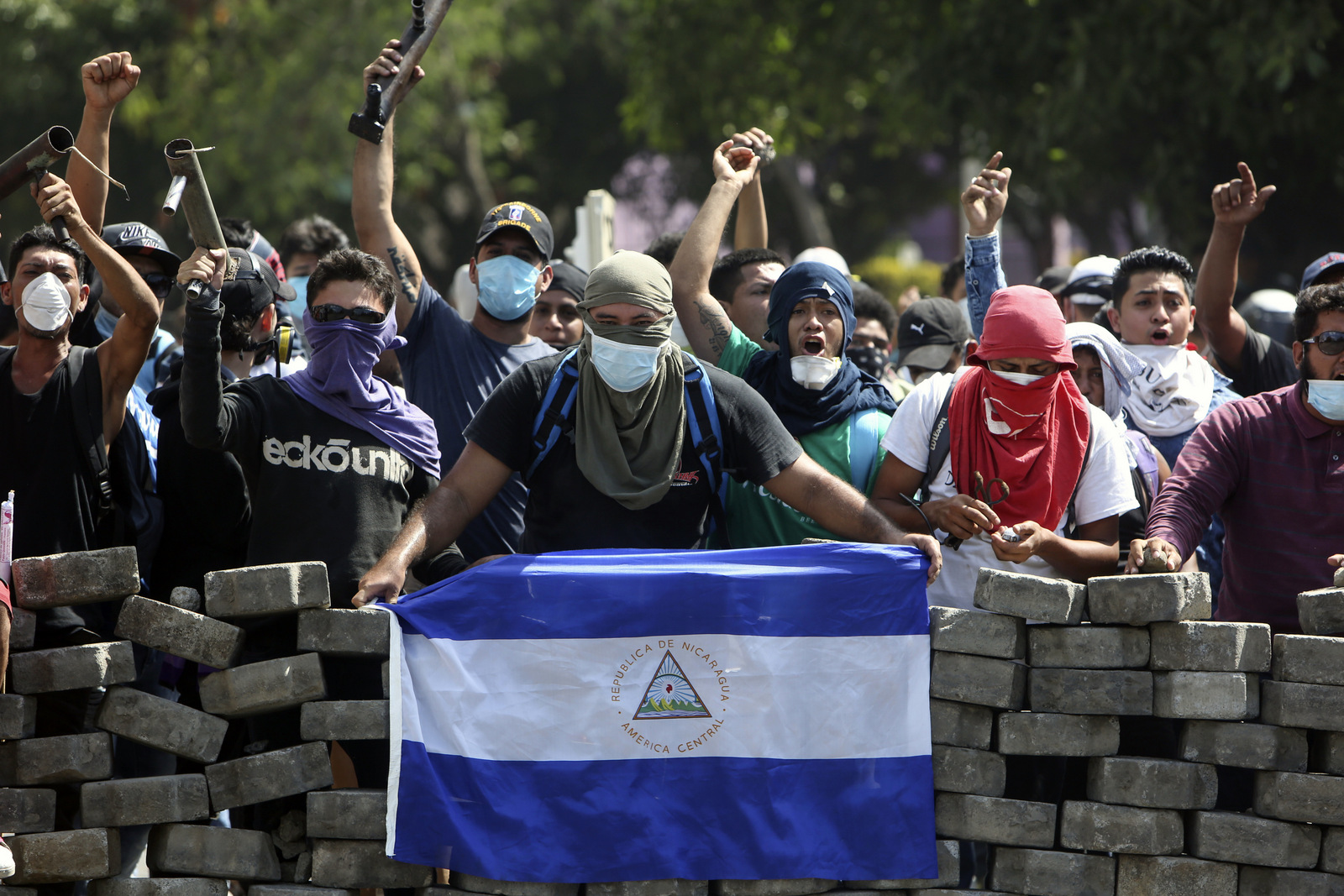Masked protesters yell from the road block they erected as they face off with security forces near the University Politecnica de Nicaragua (UPOLI) in Managua, Nicaragua, April 21, 2018. (AP/Alfredo Zuniga)