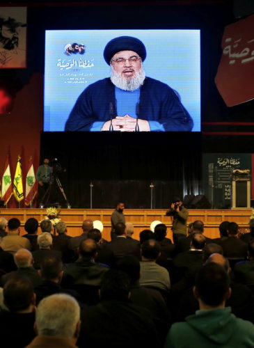 Hezbollah leader Sheik Hassan Nasrallah speaks on a screen via a video link during a ceremony to mark the anniversary of the death of Hezbollah leaders in the southern suburbs of Beirut, Lebanon, Feb. 16, 2018. (AP/Bilal Hussein)