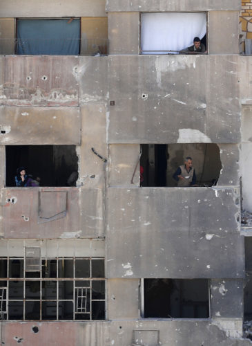 In this Monday, April 16, 2018 photo, people look out of their damage apartment windows just meters away from where the alleged chemical weapons attack occurred in the town of Douma, the site of a suspected chemical weapons attack, near Damascus, Syria. The survivors blamed the attack on the Army of Islam, the powerful rebel group that controlled the town before it was taken over by Syrian government forces this week, although they did not offer evidence to back up their claims.(AP/Hassan Ammar)