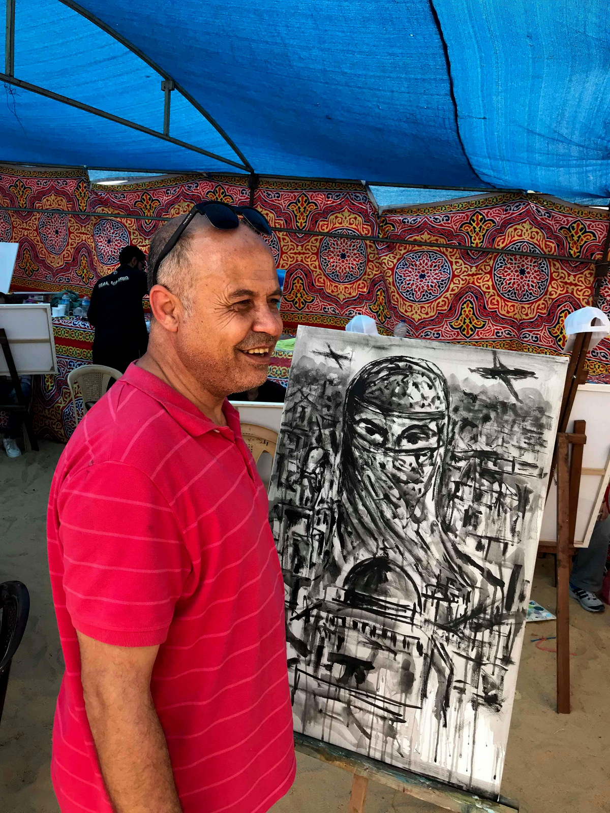 Basel el-Maqosui stands in front of his one of his paintings. (Photo: Shareef Sarhan)