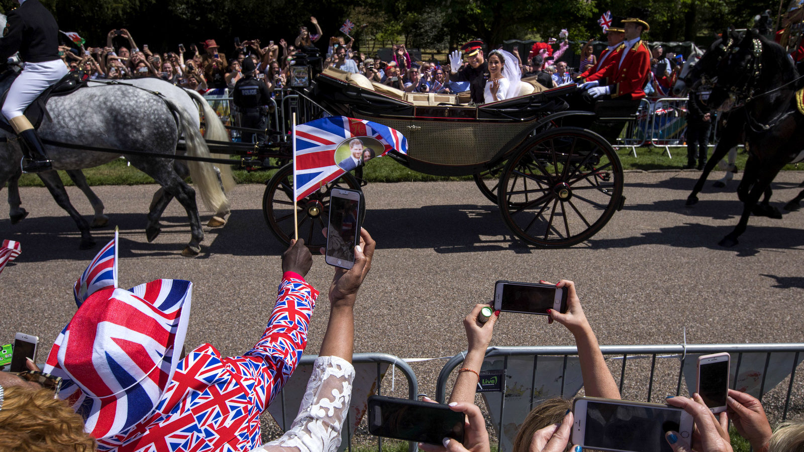 Britain's Prince Harry and Meghan Markle wave to the crowd in a carriage after their wedding ceremony at St. George's Chapel in Windsor Castle in Windsor, near London, England, May 19, 2018. (AP/Emilio Morenatti)