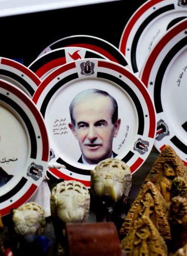 Photo, porcelain plates bearing portraits of Syrian President Bashar Assad and his father late Syrian President Hafez Assad are displayed in a souvenirs shop outside the historic 7th century Umayyad Mosque, in Damascus, Syria, April 17, 2016. (AP/Hassan Ammar)