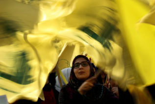 A Hezbollah supporter waves her group flags during an election campaign speech by Hezbollah leader Sayyed Hassan Nasrallah, in a southern suburb of Beirut, Lebanon, April 13, 2018. (AP/Hussein Malla)