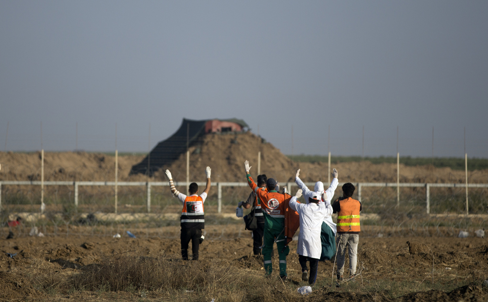 Palestinian medics raise their hands while walking towards an Israeli sniper nest near the border with Israel to evacuate injured protesters, May 15, 2018 (AP/Khalil Hamra)