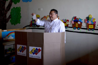 Opposition presidential candidate Javier Bertucci, a TV evangelist, shows his ballot during presidential elections in Valencia, Venezuela, Sunday, May 20, 2018. Amidst hyperinflation and shortages of food and medicine President Nicolas Maduro is seeking a second six-year term in an election that a growing chorus of foreign governments refuse to recognize after key opponents were barred from running. (AP Photo/Fernando Llano)