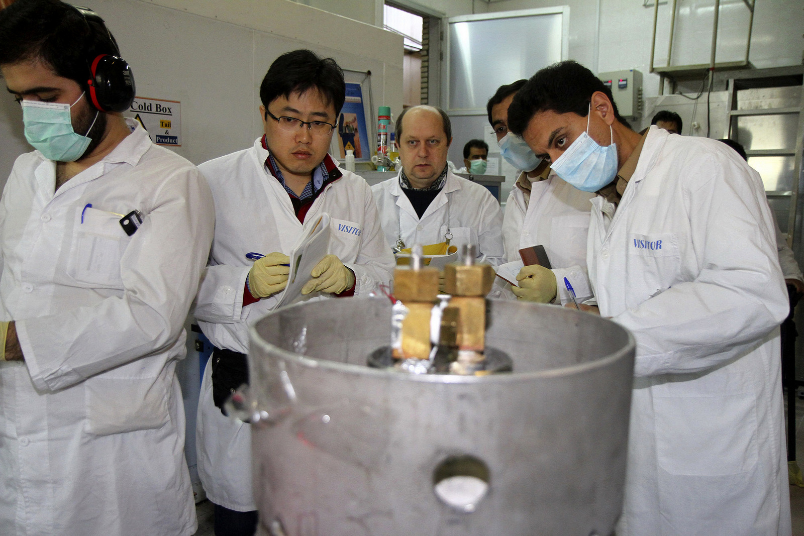 Unidentified International Atomic Energy Agency (IAEA) inspectors and Iranian technicians are on hand to cut the connections between the twin cascades for 20 percent uranium enrichment at Natanz facility, some 200 miles (322 kilometers) south of the capital Tehran, Iran, Monday, Jan. 20, 2014. Iran has halted its most sensitive uranium enrichment work as part of a landmark deal struck with world powers, state TV said Monday. The broadcast said Iran halted its 20 percent uranium enrichment, which is just steps away from bomb-making materials, by cutting the link feeding cascades enriching uranium in Natanz. (AP Photo/IRNA, Kazem Ghane)