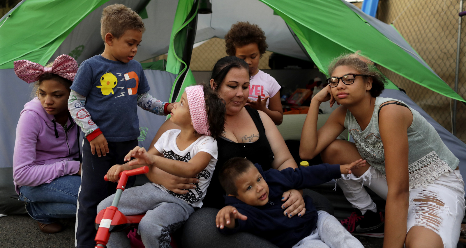 Christine Wade sits among her children in front of their donated tent in the city-sanctioned encampment on a parking lot in San Diego. They are, from left, Shawnni, 12, Roland, 4, Rayahna, 3, Jaymason, 2, Brooklyn, 8, and Shaccoya, 14. The Wade family is among several hundred people living in the city's first campground open for the homeless, set up to curb the worst Hepatitis A outbreak in the United States in decades. Gregory Bull | AP
