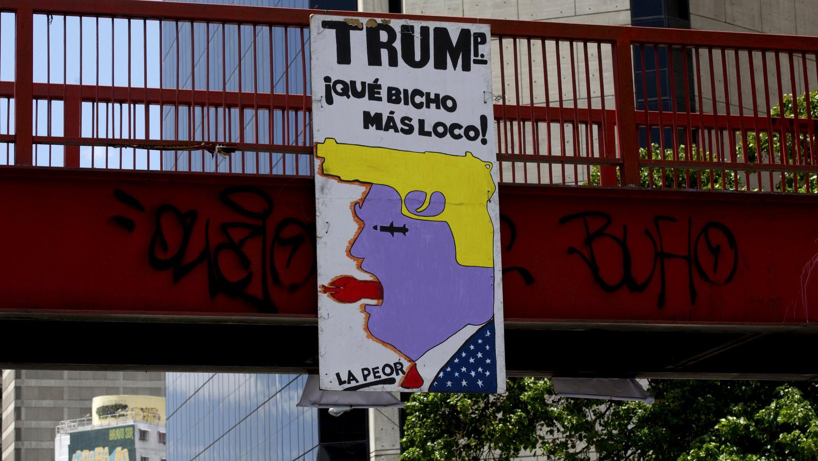 Знак с изображением, представляющим президента США Дональда Трампа, и текст, который читается на испанском языке «Трамп, какой сумасшедший тварь!» висит от моста в Каракасе, Венесуэла, 8 марта 2018 года. Фернандо Льяно | AP