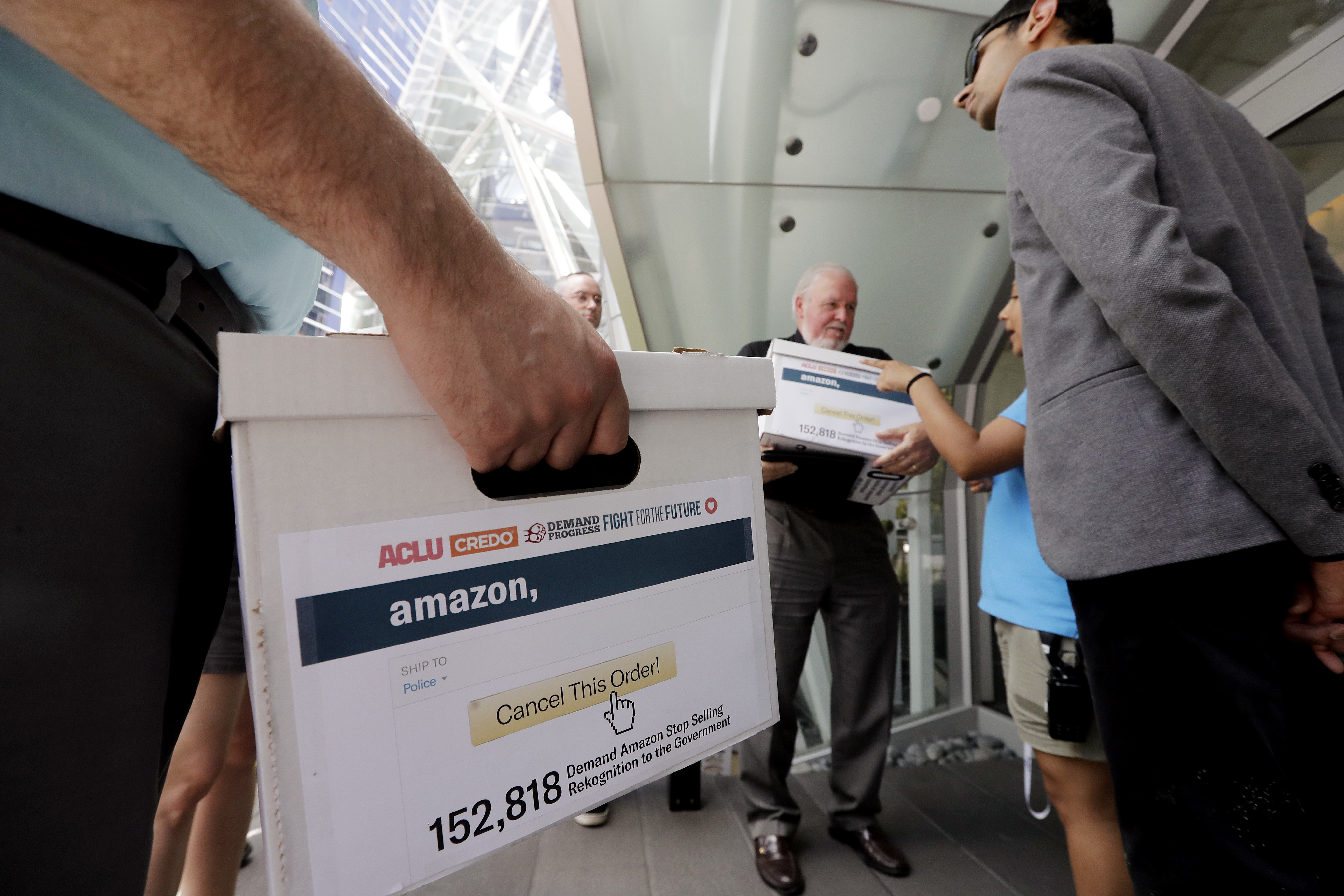 Rev. Paul Benz, center, and Shankar Narayan, legislative director of the ACLU of Washington, right, stand with others as they wait to deliver petitions at Amazon headquarters, June 18, 2018, in Seattle. Representatives of community-based organizations urged Amazon at a news conference to stop selling its face surveillance system, Rekognition, to the government. They later delivered the petitions to Amazon. Elaine Thompson | AP