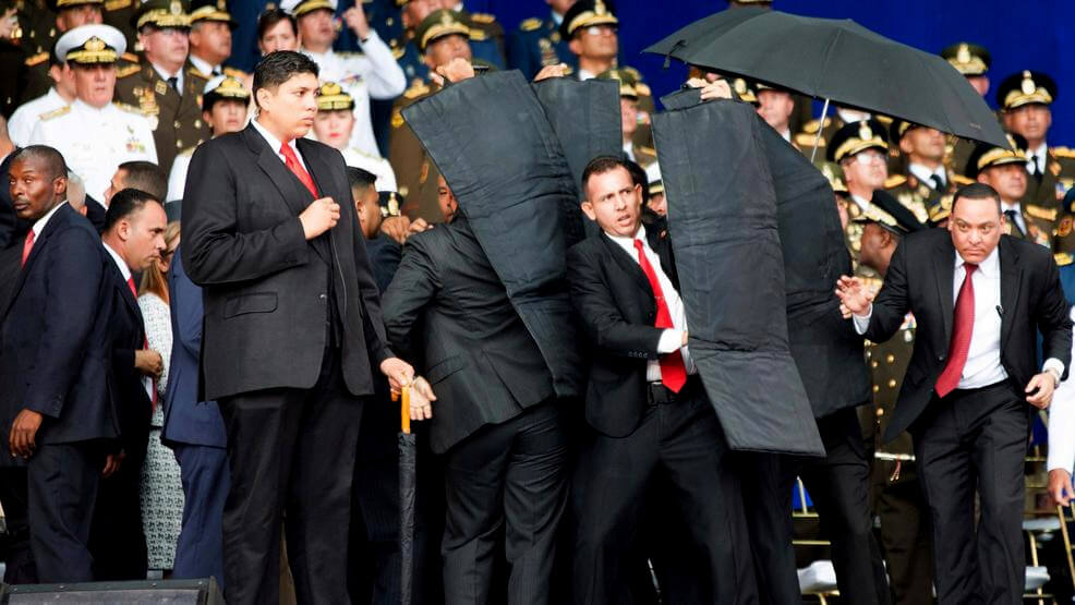 In this photo released by China's Xinhua News Agency, security personnel surround Venezuela's President Nicolas Maduro during an incident as he was giving a speech in Caracas, Venezuela, Aug. 4, 2018. Drones armed with explosives detonated near Venezuelan President Nicolas Maduro as he gave a speech to hundreds of soldiers in Caracas on Saturday but Maduro was unharmed. Xinhua via AP