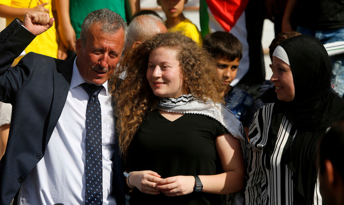 Ahed Tamimi stans between her father Bassam and mother Nariman during a press conference on the outskirts of the West Bank village of Nabi Saleh near the West Bank city of Ramallah, July 29, 2018. Palestinian protest icon Ahed Tamimi and her mother Nariman returned home to a hero's welcome in her West Bank village on Sunday after Israel released the 17-year-old from prison at the end of her eight-month sentence for slapping an Israeli soldier .Majdi Mohammed | AP
