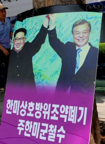 Photos showing North Korean leader Kim Jong Un, left, and South Korea President Moon Jae-in are displayed to demand withdrawal of U.S. troops from Korean Peninsula near the U.S. Embassy in Seoul, South Korea, Aug. 13, 2018. Ahn Young-joon | AP