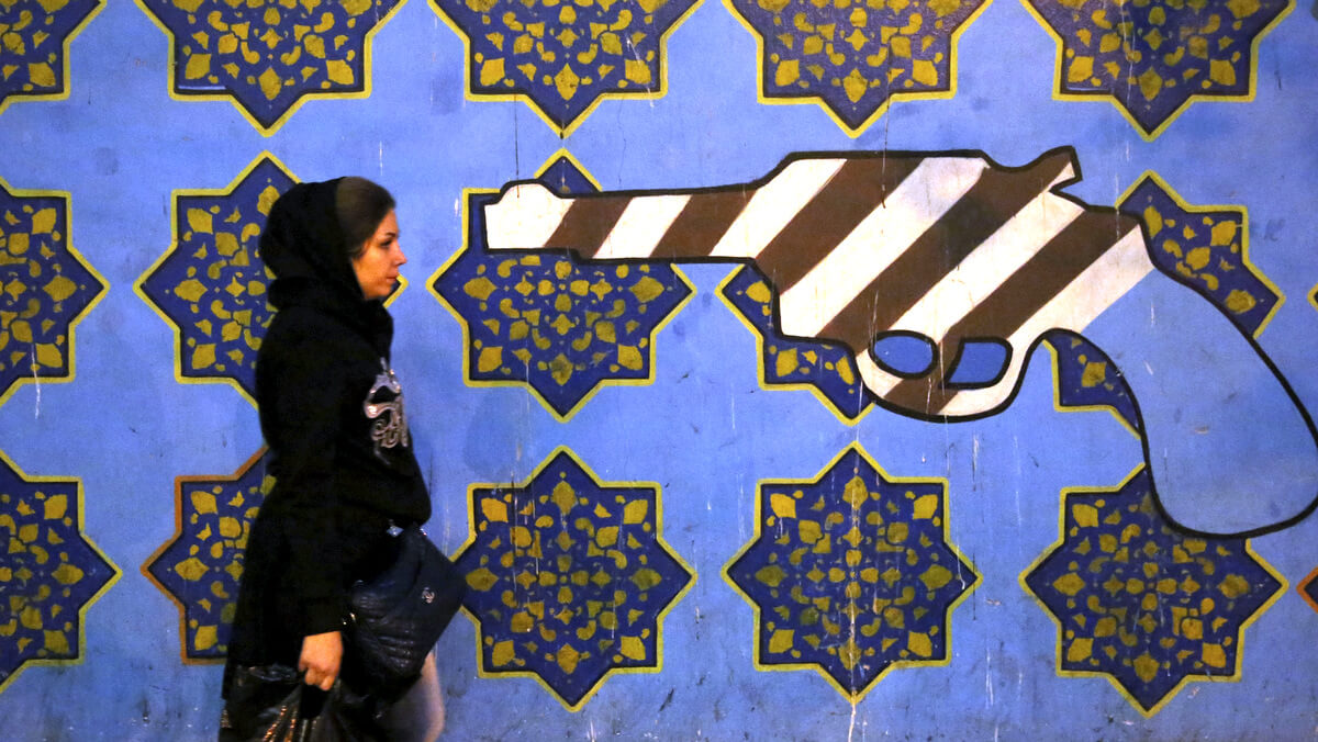 An Iranian woman walks past a mural, painted on the wall of the former U.S. Embassy, in Tehran, Iran, Nov. 2, 2013. Ebrahim Noroozi | AP