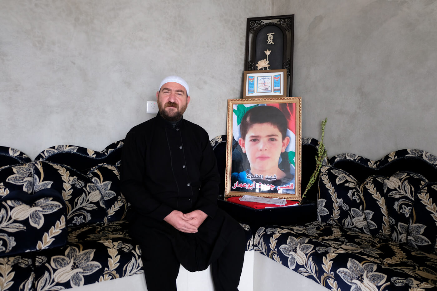 Jawdat Abo Ammar next to the photo of his martyred son, Qussai, fatally injured during the SAA rescue operation in Tilal Al-Safa. Photo | Vanessa Beeley
