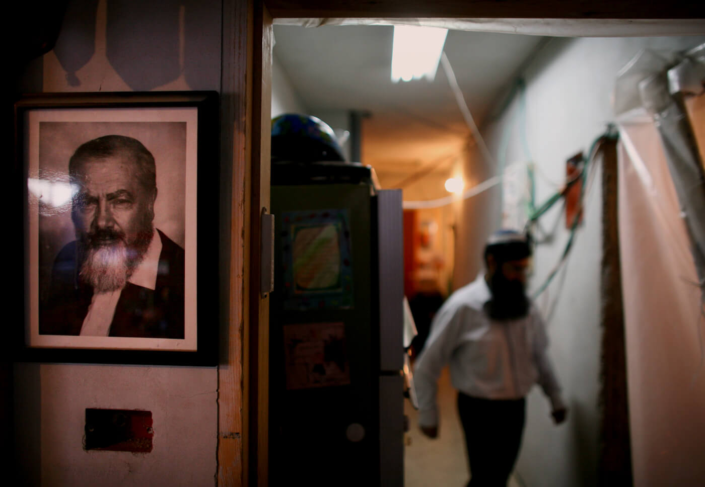 With a portrait of late Rabbi Meir Kahane on the wall, left, a Jewish settler walks inside a building taken from a Palestinian family in Hebron, Nov. 16, 2008. Dan Balilty | AP