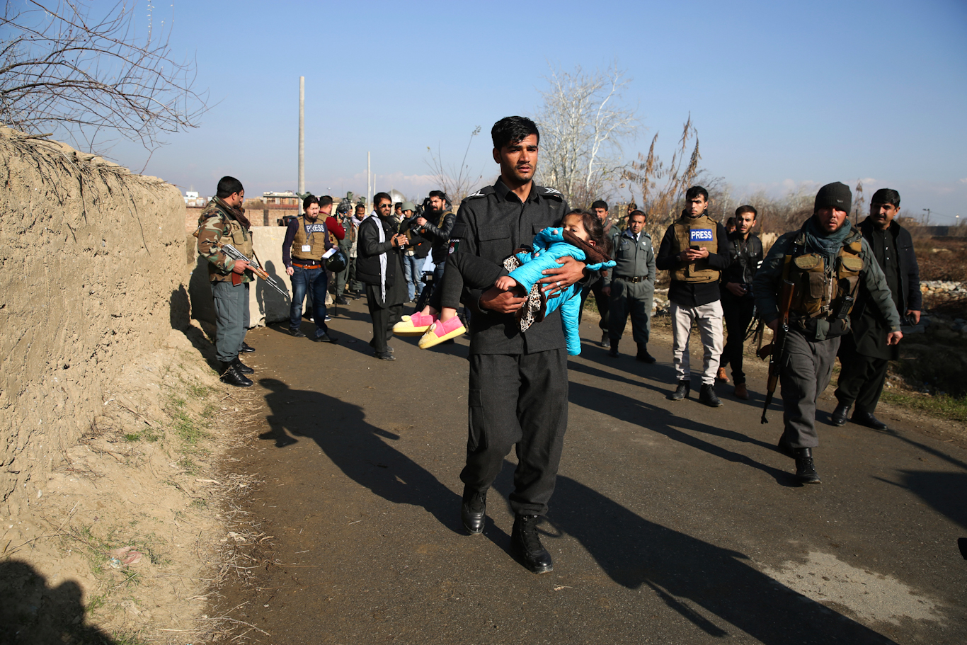 A police officer carries his injured daughter after an attack near a U.S. Air Base In Parwan province of Kabul, Afghanistan, Dec. 11, 2019. Rahmat Gul | AP